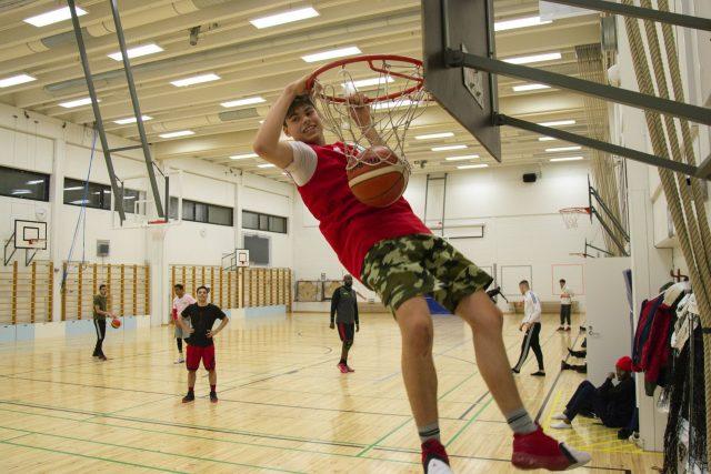 poika roikkuu koripallokorissa