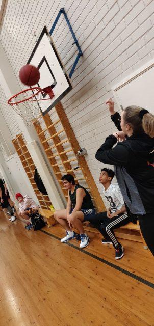 tyttö heittää koripalloa