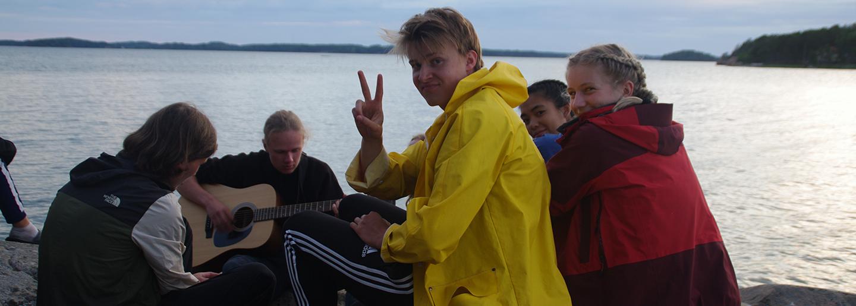 nuoret istuvat meren rannassa