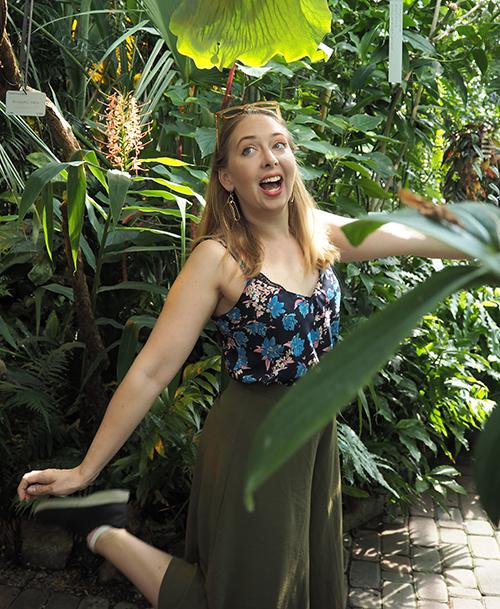 nainen poseeraa viherkasvien edessä